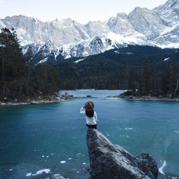 жена на скала в езеро сред зимен пейзаж